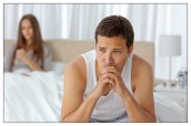 Pensive man having a headache sitting on the bed with his girlfriend on the background